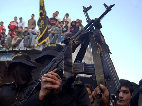 Armed members of the Islamic Jihad movement stand with their rifles aloft during a demonstration in the northern West Bank city of Nablus, in support of their leader Ramadan Shallah, who is based in Damascus, Syria, Friday Feb. 16, 2007. The United States' State Department this week offered up to $5 million for information leading to the arrest of Shallah, who is wanted for complicity in suicide bombings, murder, extortions and money laundering according to the agency. Responding to the State Department's announcement, Islamic Jihad said it would attack American targets if Shallah is taken into custody. (AP Photo/Majdi Mohammed)